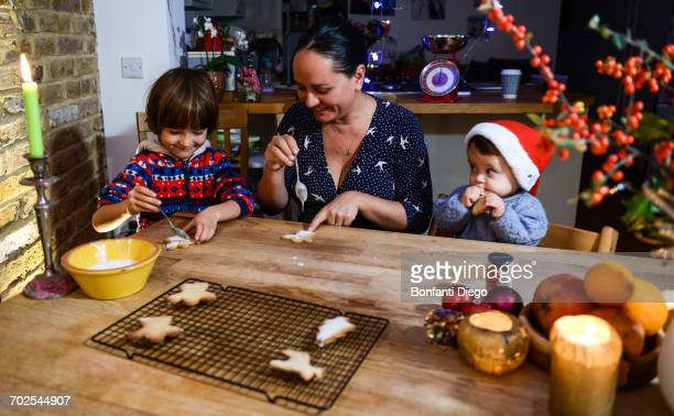 Mother and two sons at table icing home-baked Christmas biscuits