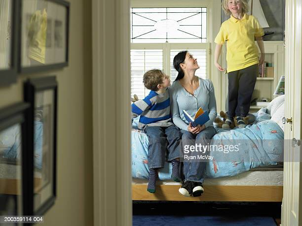 Mother and two sons (5-8) reading in bedroom, one boy jumping on bed