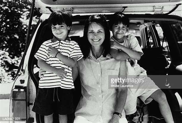 Mother and two young children (5-7) in family car, portrait (B&W)