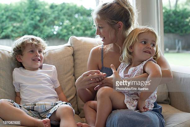 Mother and two young children sitting together on sofa