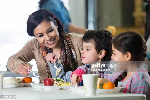 Madre e bambini avendo pasto in beneficenza Mensa per i poveri