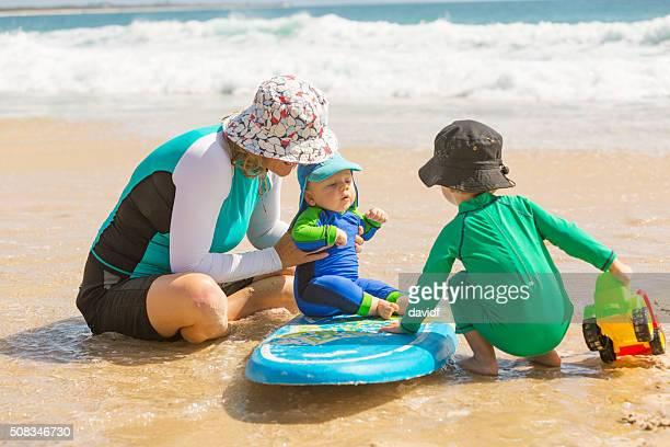 Mutter und junge Kinder spielen am Strand