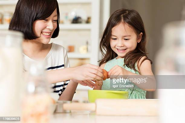 Mother and young daughter cracking egg into mixing bowl