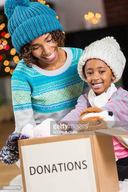 Mutter und junge Tochter an Wohltätigkeitsorganisationen spenden Sie Spielzeug für Weihnachten