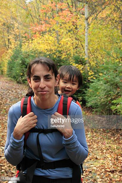 Mother and Young Daughter Hiking Through Colorful Forest