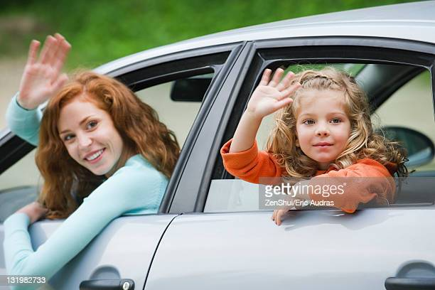 Mother and young daughter leaning out of car windows, waving