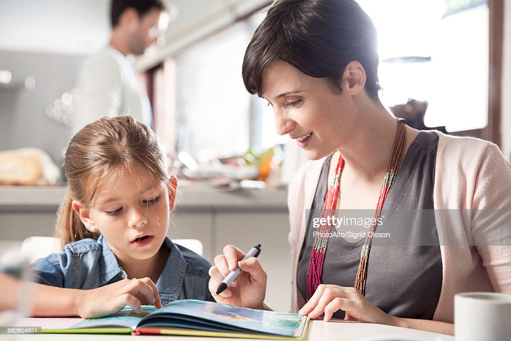 Mother and young daughter reading together : Stock Photo