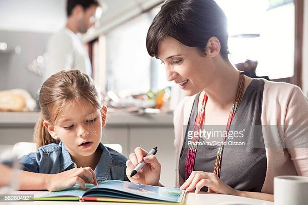 Mother and young daughter reading together