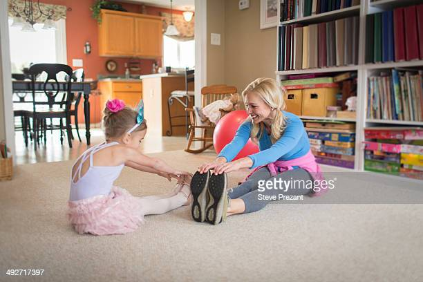 Mother and young daughter warming up for ballet in sitting room