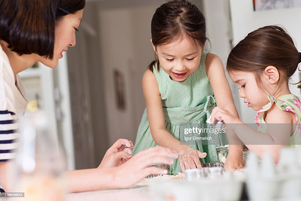 Mother and young daughters making pastry : Stock Photo