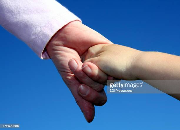Mother And Young Son Holding Hands On Blue Background