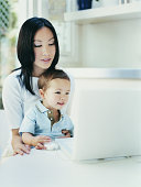 Mother and Young Son Sitting at a Dining Room Table Using a Laptop