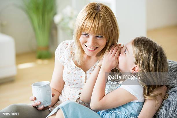 Mother ans daughter sitting on couch with drinking cups