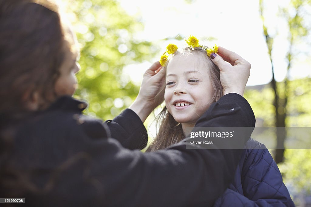 Mother applying flower wreath to daughter's head : Stock Photo
