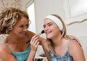 Mother applying make up to daughter (13-15) smiling