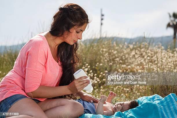 Mother applying suncream to baby's chest