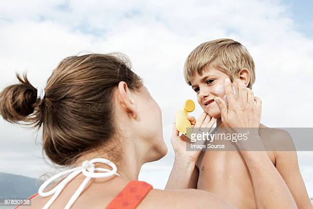 Mother applying suncream to son