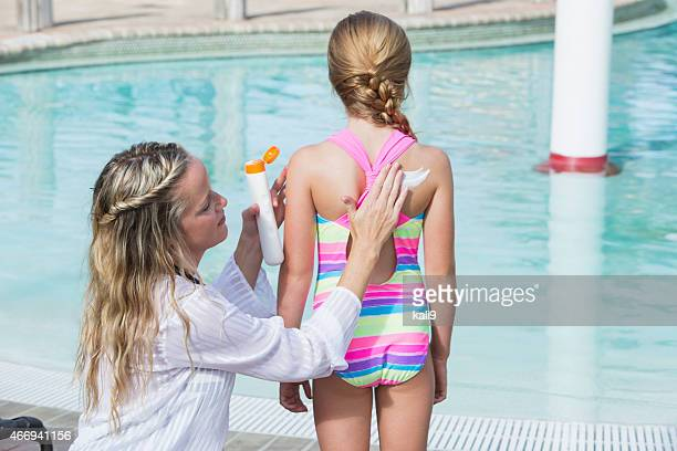 Mother applying sunscreen on child at pool