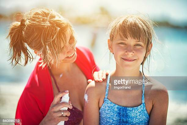 Mother applying sunscreen on daughter