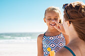 Young mother applying protective sunscreen on daughter nose at beach. Woman hand putting sun lotion on child face. Cute little girl with sunblock at seaside with copy space.