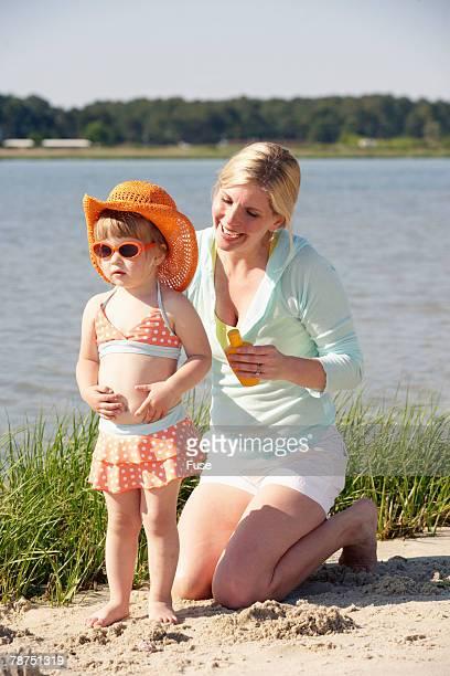 Mother Applying Suntan Lotion on Daughter's Back