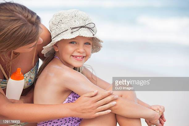 Mother applying suntan lotion on daughter's hand