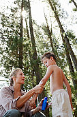 Mother Applying Suntan Lotion to Son