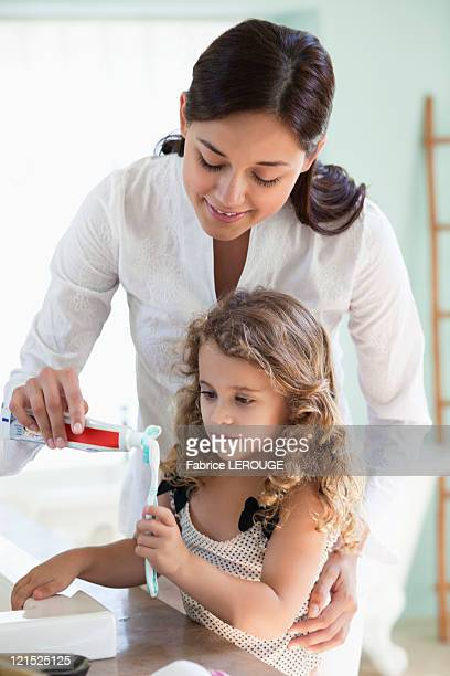 Mother applying tooth paste on little girls tooth brush at bathroom
