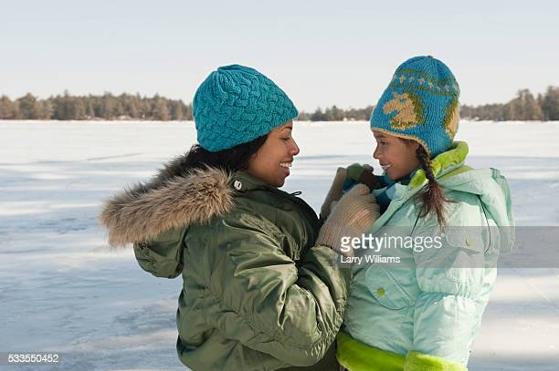 Mother assisting daughter with coat