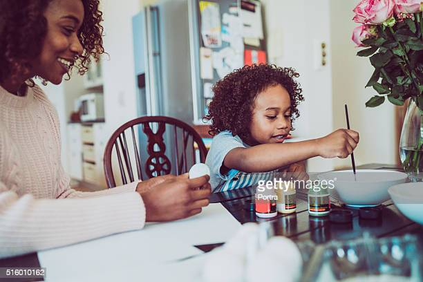 Mother assisting girl in painting Easter egg at home
