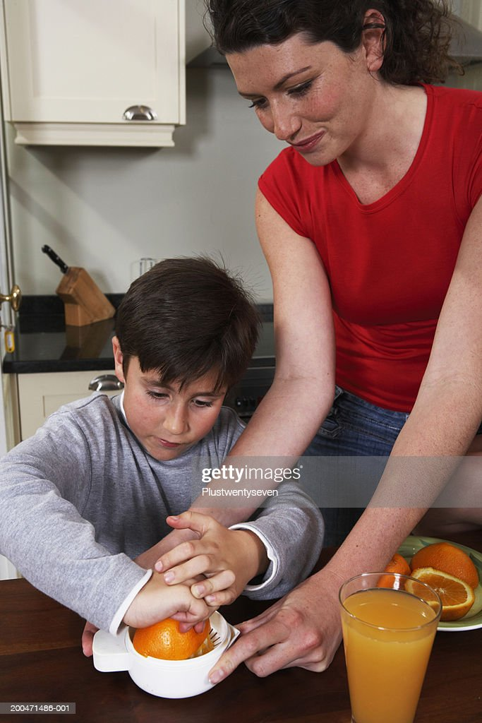 Mother assisting son (6-8) squeeze orange in kitchen : Stock Photo