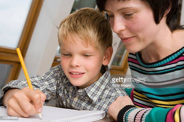 Mother assisting son with homework