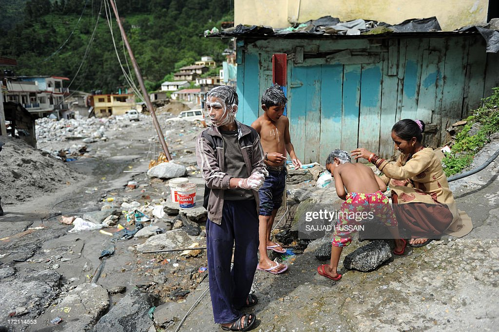 A mother bathes her children on the roadside in Sonprayag on July 2, 2013, in a flood affected area of the northern Indian state of Uttrakhand. Construction along river banks will be banned in a devastated north Indian state amid concerns unchecked development fuelled last month's flash floods and landslides that killed thousands, the state's top official said. The Chief Minister of Uttarakhand, Vijay Bahuguna, also announced that a regulatory body would be set up to scrutinise future construction as the Himalayan state begins the herculean task of rebuilding following the June 15 floods.