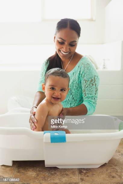 Mother bathing baby son in tub