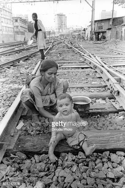 Mother bathing her son on railway tracks at Wadala, Bombay Mumbai, Maharashtra, India