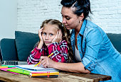 Mother becoming frustrated with daughter whilst doing homework sitting on sofa At home in learning difficulties homework parenting and education concept