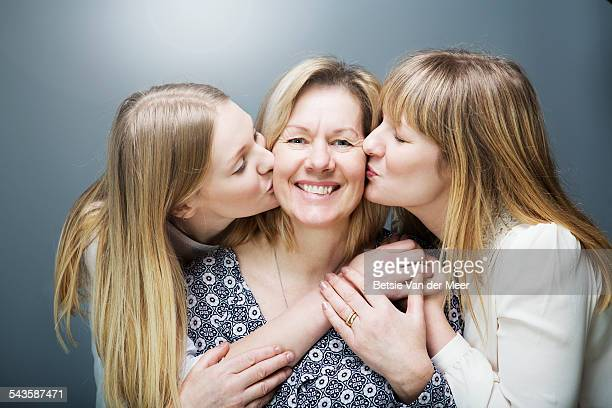 Mother being kissed by daughters on both cheeks.