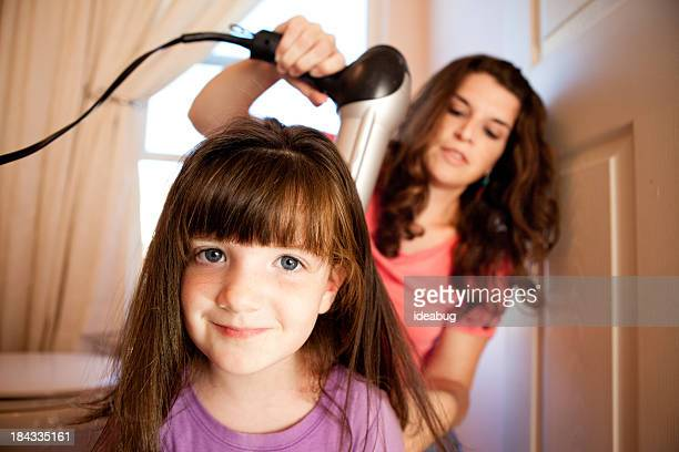 Mother Blow Drying Daughter's Hair in Bathroom at Home