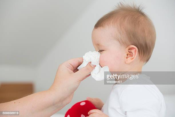 Mother blowing baby girls nose