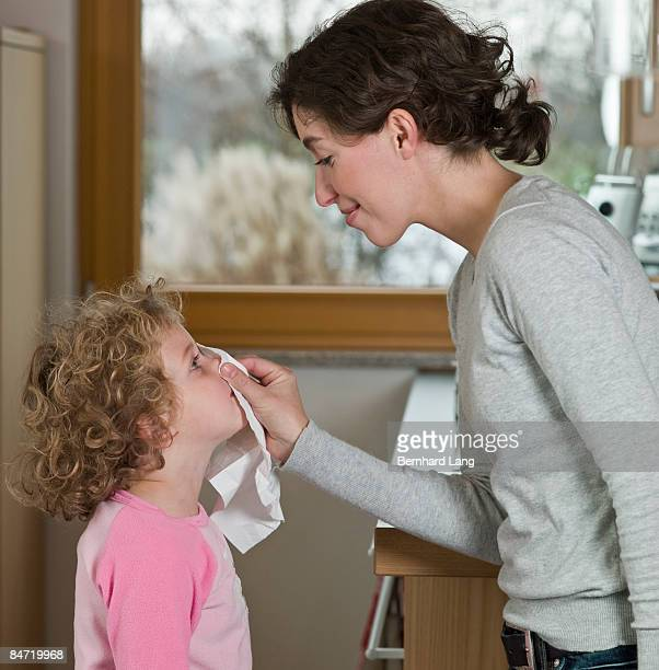 Mother blowing daughter's nose