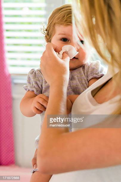 Mother blowing the nose of her baby girl.