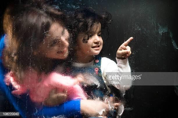 Madre con figlia di fissaggio alla finestra di cabina doccia