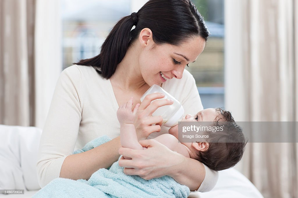 Mother bottle feeding baby boy