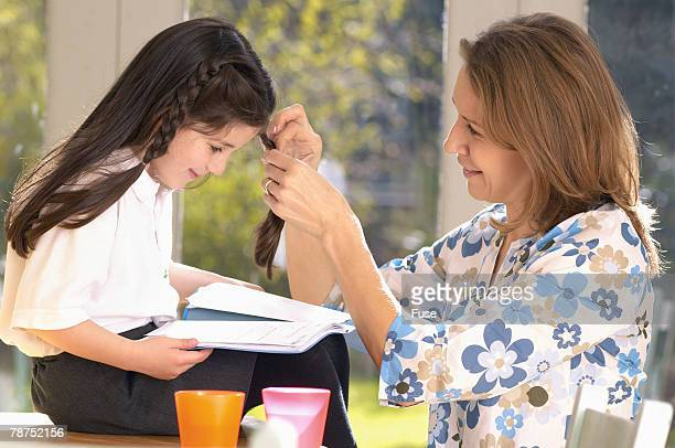 Mother Braiding Daughter's Hair