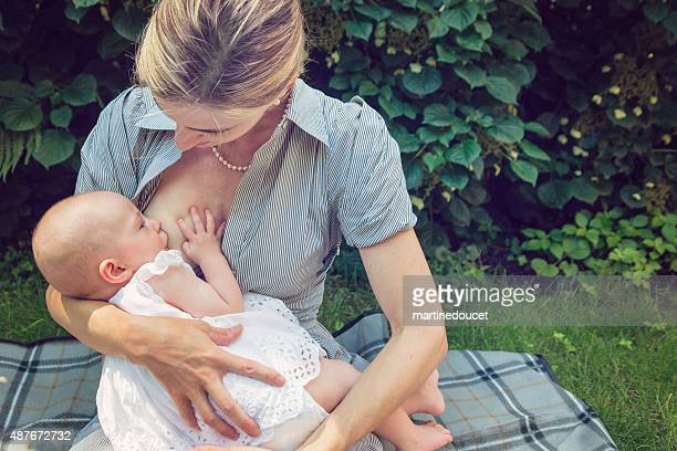 Mother breastfeeding baby girl outdoors in summer nature.