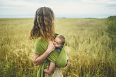 A young mother is breastfeeding her baby in a field