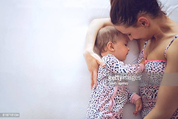 Mother breastfeeding her baby in bedroom