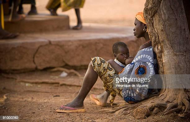 A mother brestfeeding her baby in the streets of Ouagadougou BurkinaFaso