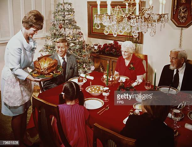A mother bringing a large turkey to the table for Christmas dinner circa 1965