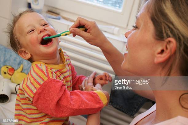 Annette Wassermann brushes the teeth of her son Leander 16 months at their home May 9 2006 in Berlin Germany Wassermann and her husband Kostas Kosmas...